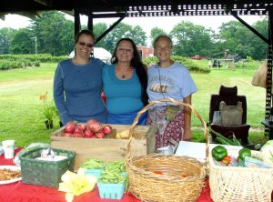 3 women at an outdoor table with baskets and boxes of fresh produce